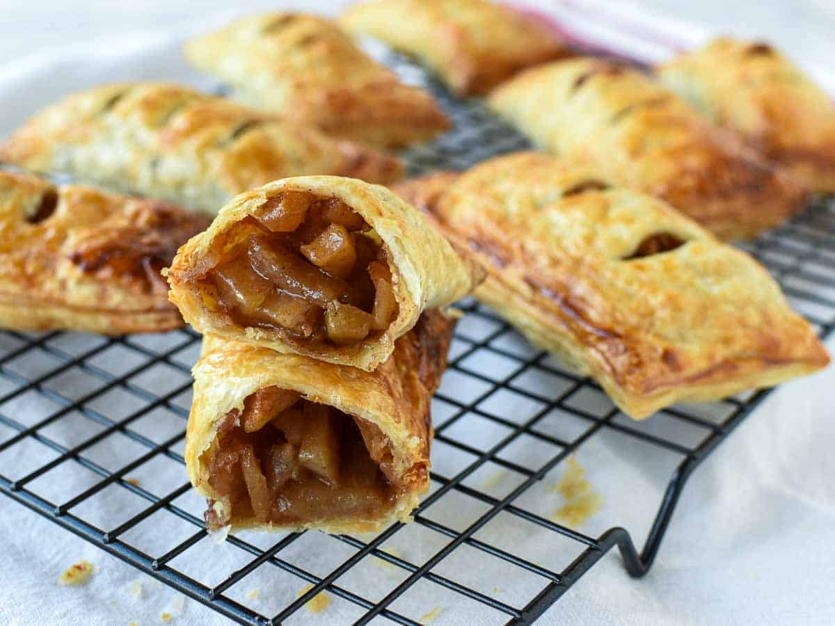 puff pastry apple turnovers on a black wire cooling rack with one turnover cut in half to reveal the inside