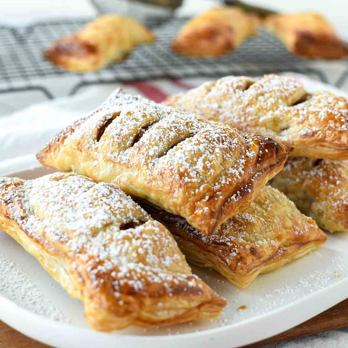 puff pastry apple turnovers on a white plate dusting with powdered sugar