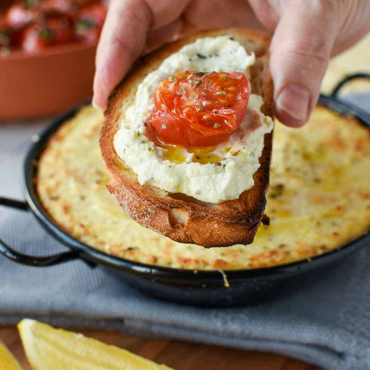 slice of toasted bread spread with baked ricotta and topped with half a slice of roasted cherry tomato