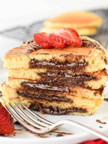 five stacked nutella filled pancakes on white plate sliced in half showing the nutella oozing out