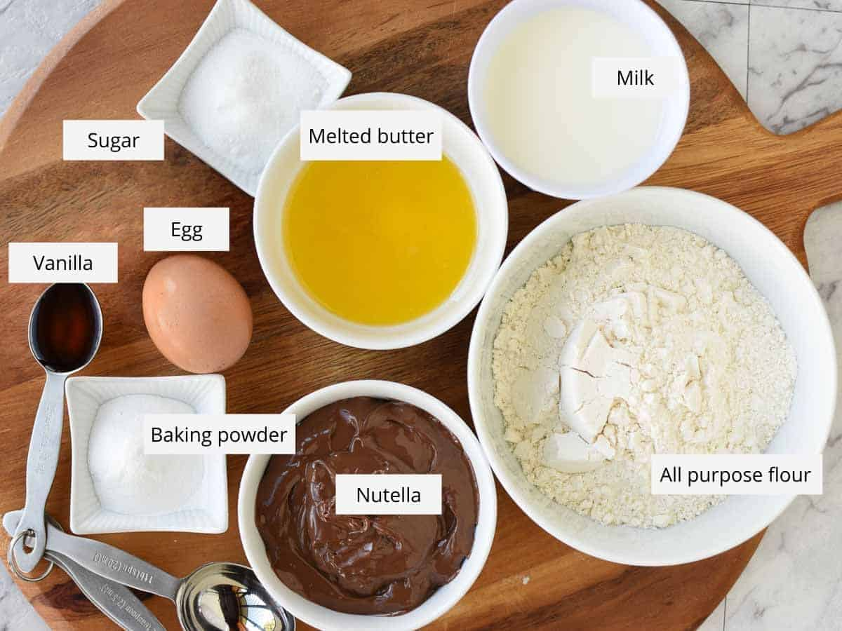 sugar, melted butter, milk , flour, nutella, baking powder, egg and vanilla in bowls viewed from above