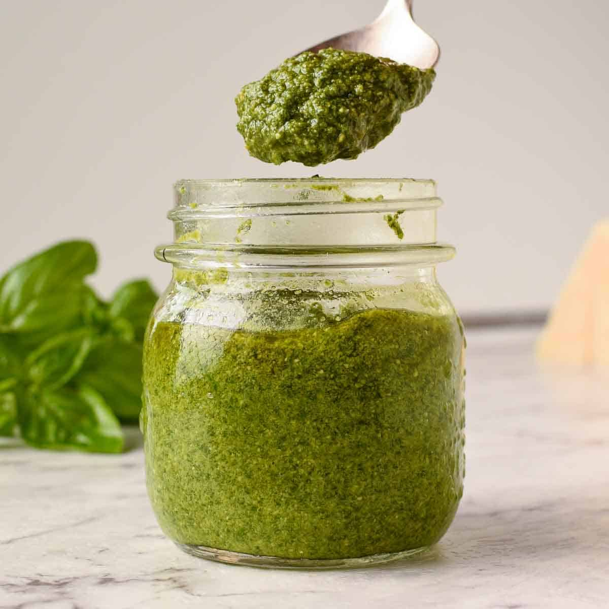 glass jar of basil pesto with a spoonful being spooned out, fresh basil in the background
