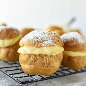 pastries filled with custard on black wire rack viewed from front on