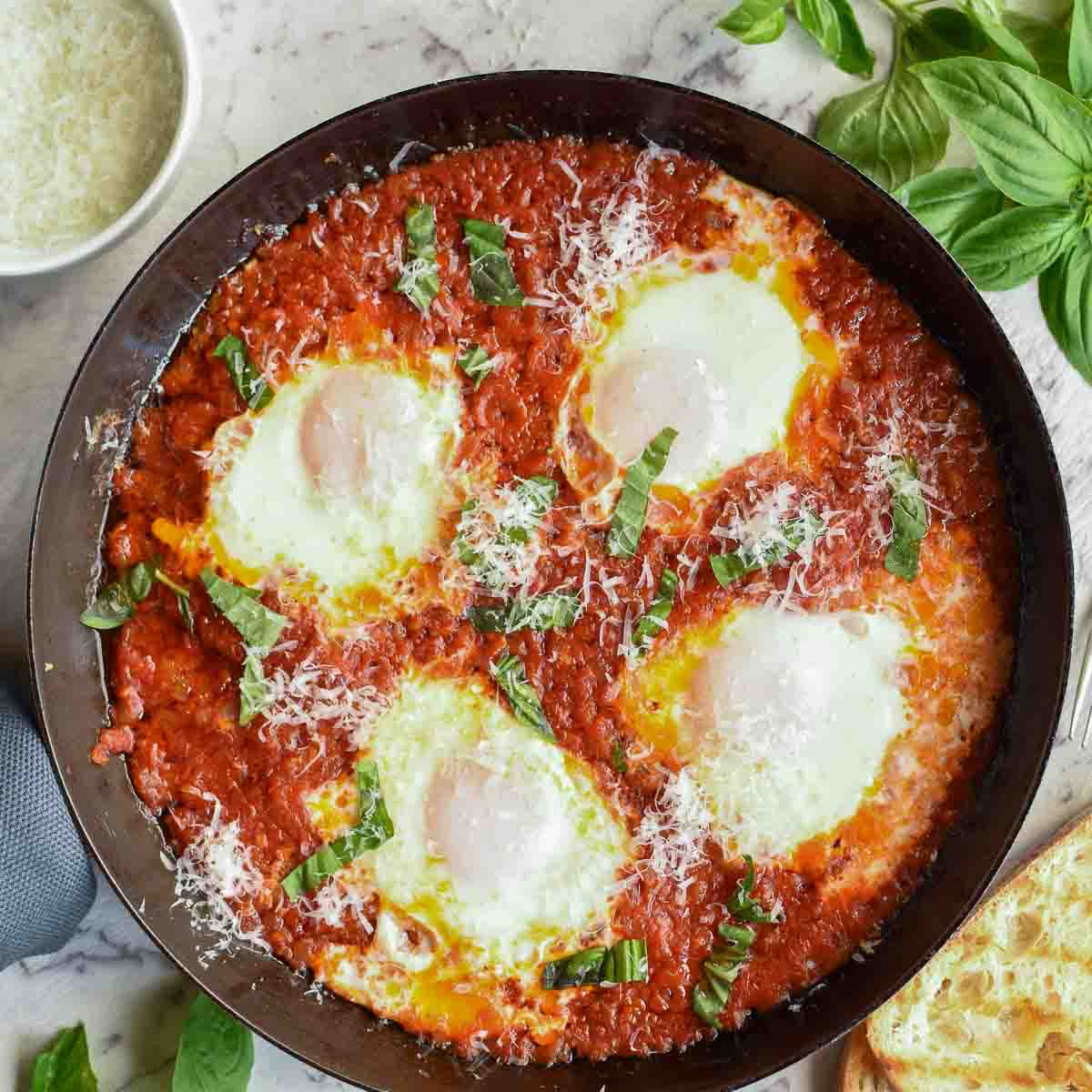 four poached eggs in tomato sauce in black pan viewed from above