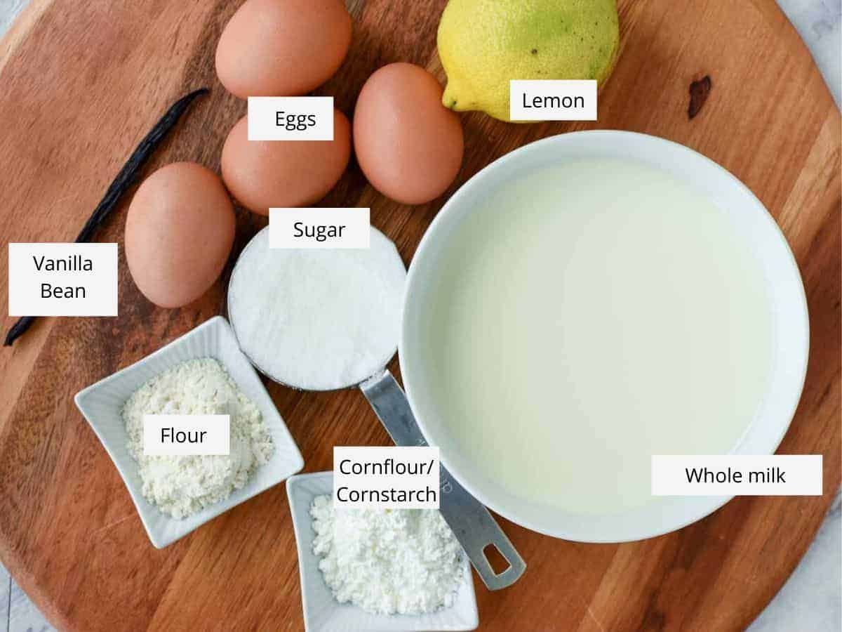 Ingredients viewed from above - eggs, lemon, milk, sugar, flour, cornflour/cornstarch, vanilla bean