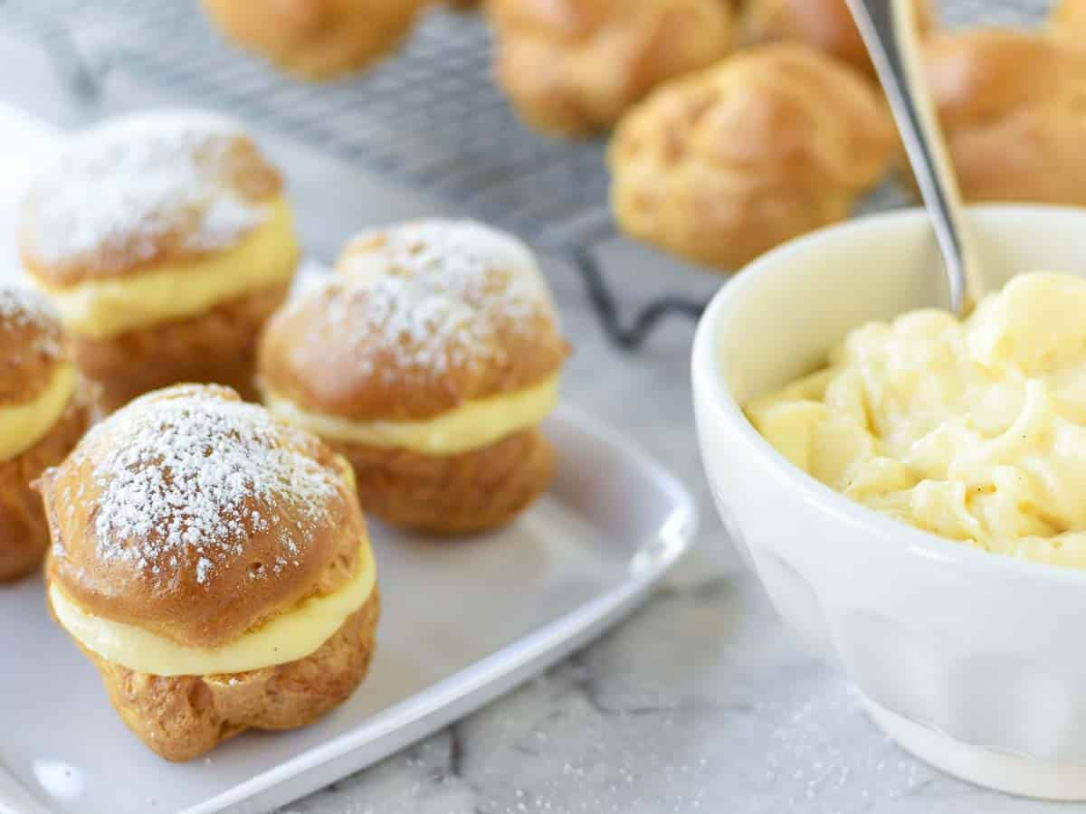 pastries filled with custard on white plate, white bowl of custard and unfilled pastries in the background