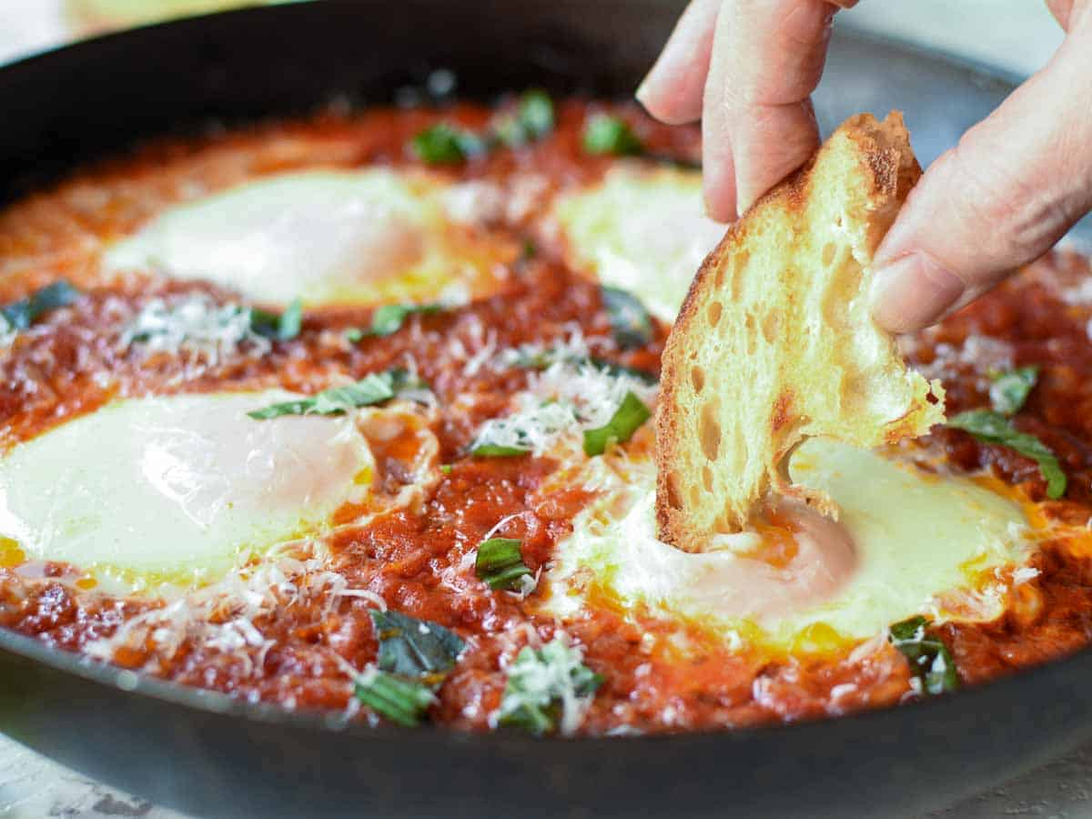 Poached eggs in tomato sauce in black pan, fingers holding toasted bread dipping into egg