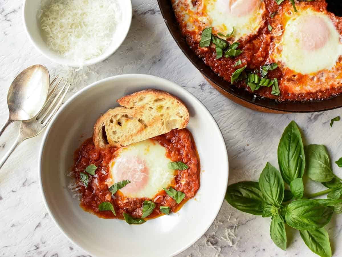 poached egg in tomato sauce and slice of toasted bread in grey bowl, black pan of eggs and tomato sauce partly out of the picture viewed from above.