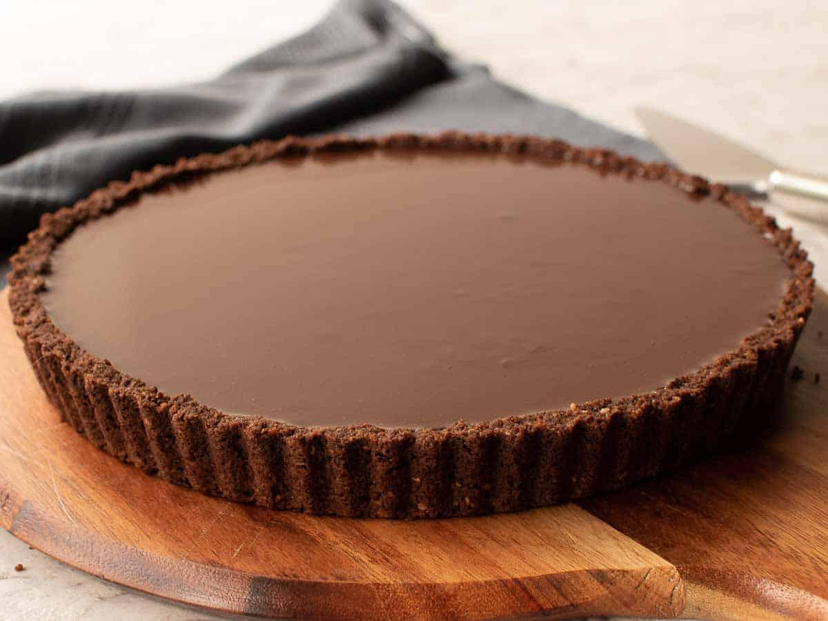 chocolate tart on wooden board.
