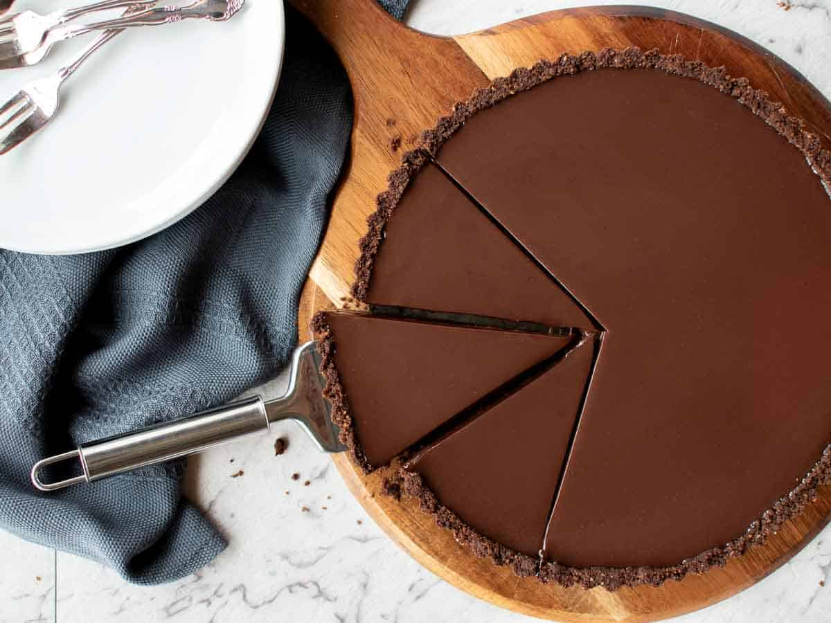 whole chocolate tart with 3 slices cut.