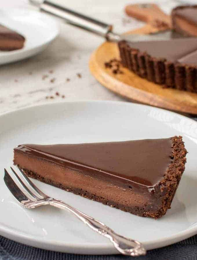slice of chocolate tart with whole tart in the background