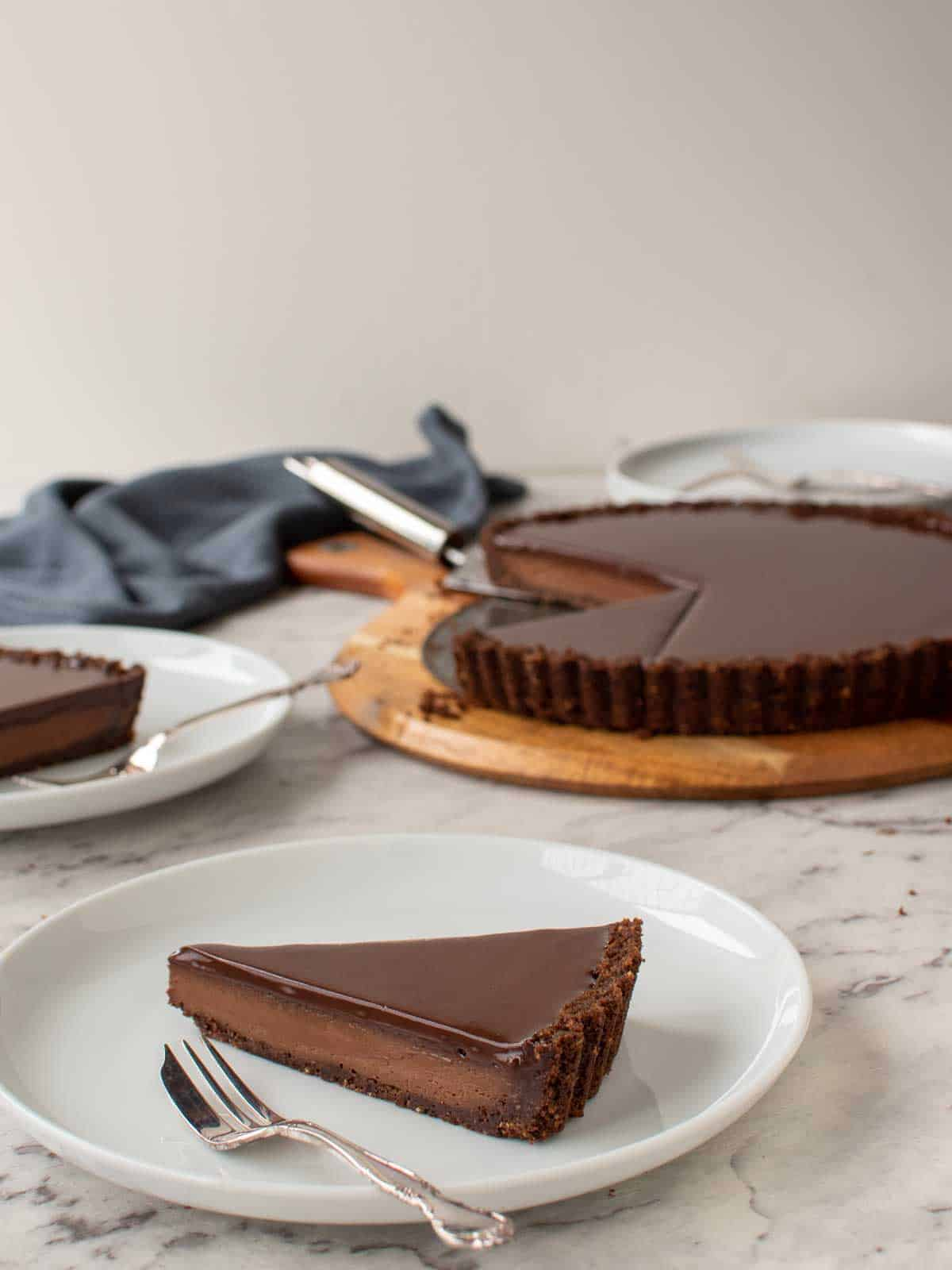 slice of chocolate tart with whole tart in the background.