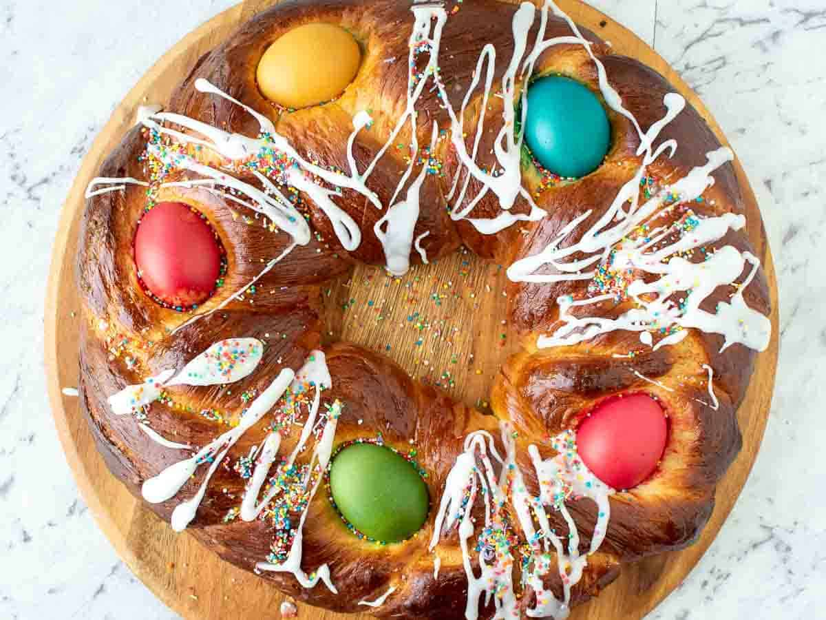 baked sweet bread decorated with red, blue, yellow and green eggs and drizzle of icing. Viewed from above