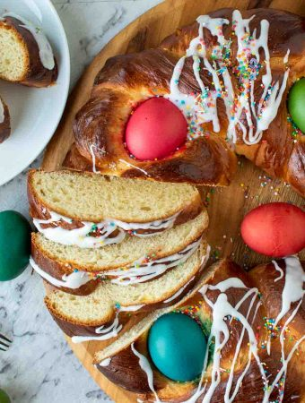 close up of baked sweet bread decorated with red, blue, yellow and green eggs and drizzle of icing and a few slice cut to show inside of bread. In the top left hand corner is two slice of the bread on a white plate. Viewed from above