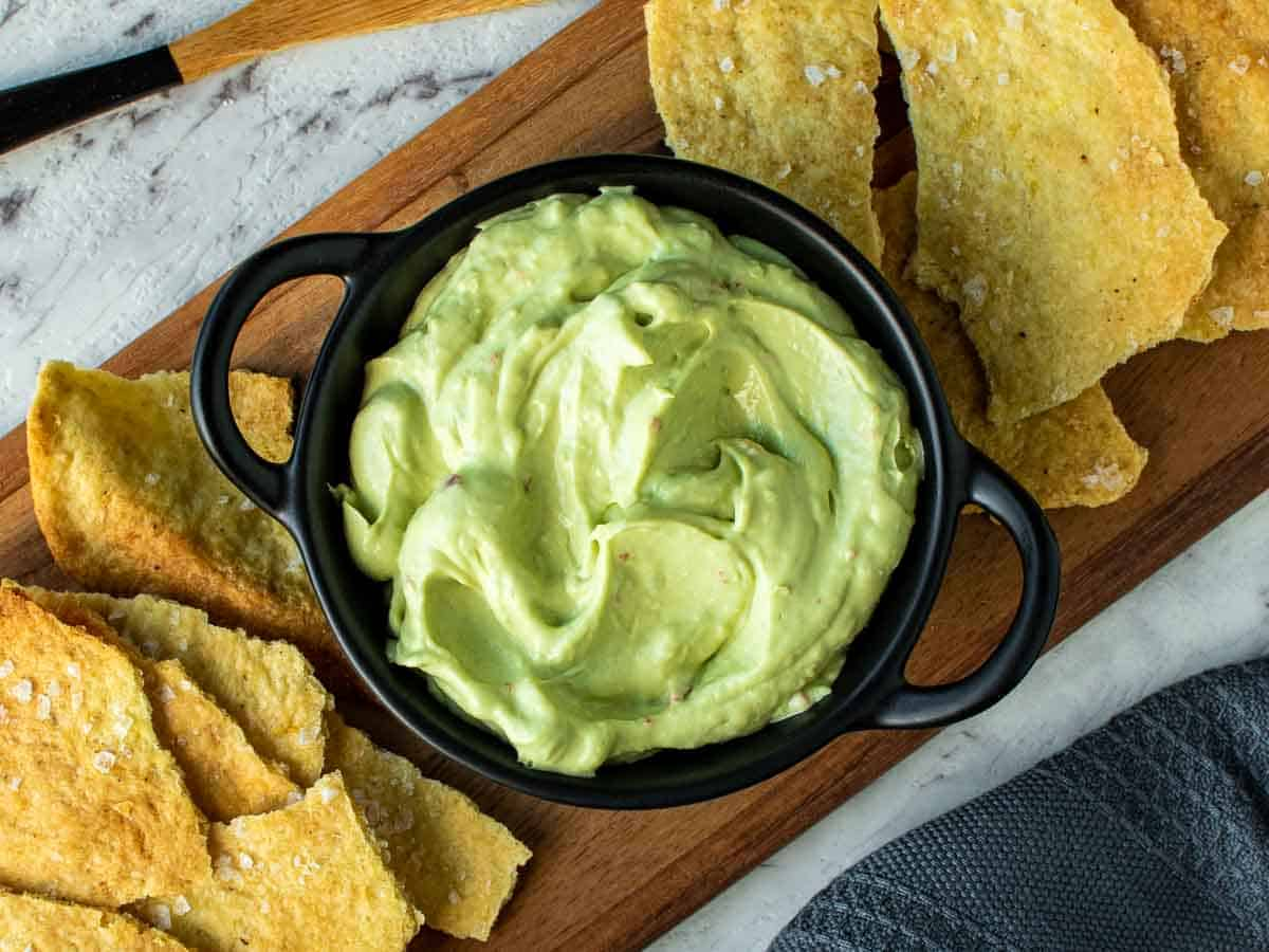 avocado dip in black bowl on wooden board surrounded by crackers viewed from above.