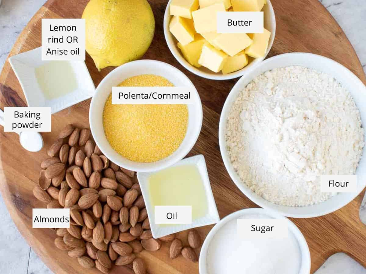 butter, flour, sugar, oil, almonds, baking powder, anise oil, lemon and cornmeal in bowls on wooden board.