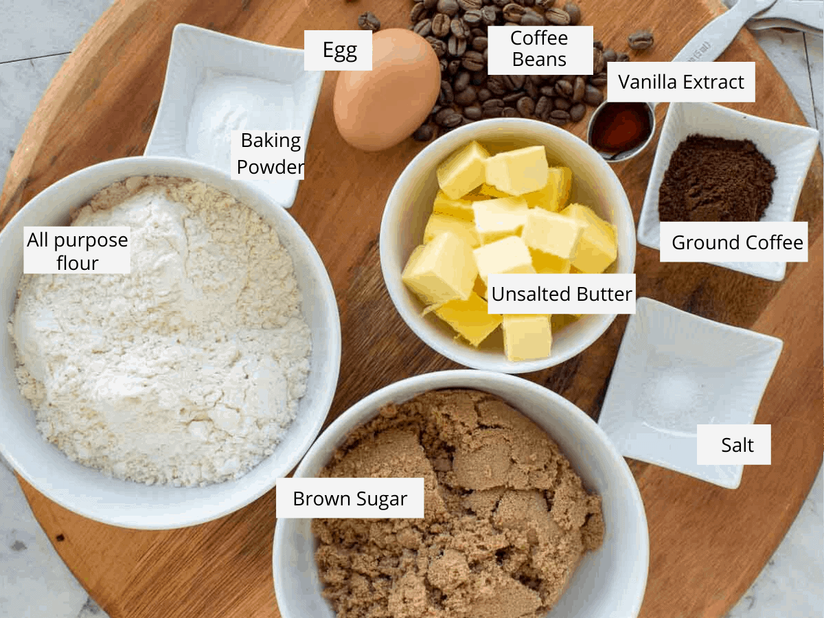 flour, baking powder, an egg, coffee beans, vanilla extract in a spoon, ground coffee, salt, brown sugar and unsalted butter in white bowls all on wooden board
