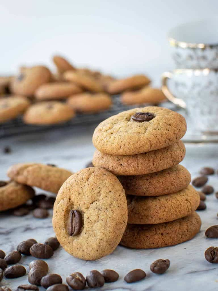 five cookies stacked with a sixth cookies leaning on the stack - cookies in the background and coffee beans scattered around