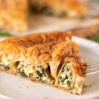 slice of spinach ricotta filo pie on white plate with fork piercing the edge