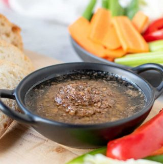 Bagna cauda sauce in a black dish surrounded by sliced vegetables and bread
