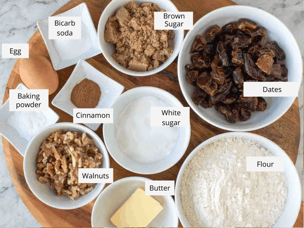 ingredients on wooden board - baking powder, brown and white sugar, dates, flour, butter, walnuts, baking soda, egg and cinnamon