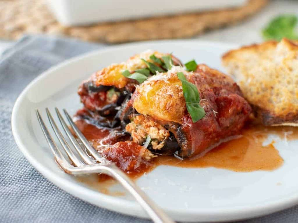 two eggplant involtini on a white plate with fork