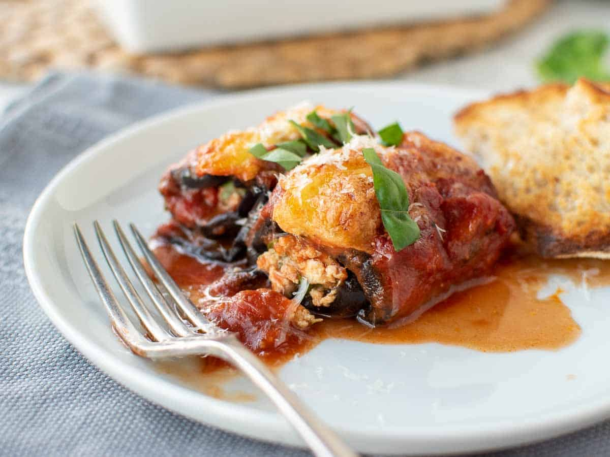 two eggplant involtini on a white plate with fork.