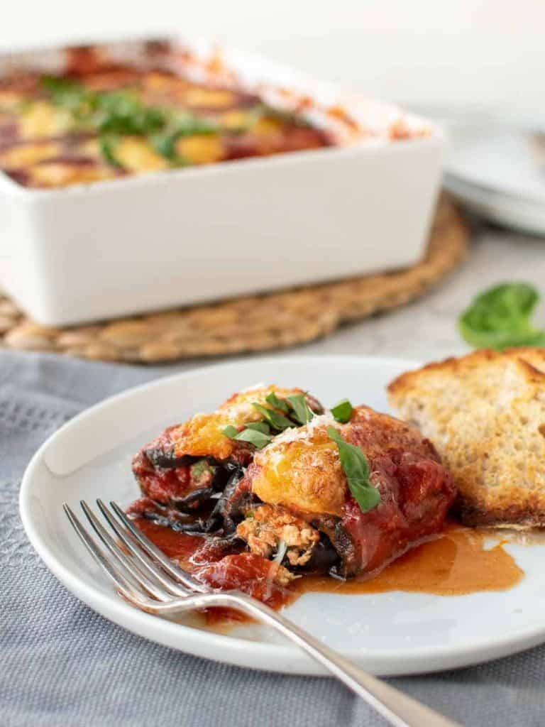 two eggplant involtini on a white plate with fork with white baking dish in the background