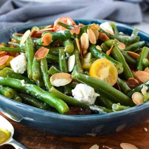 green bean salad with tomatoes and feta in blue bowl on wooden board