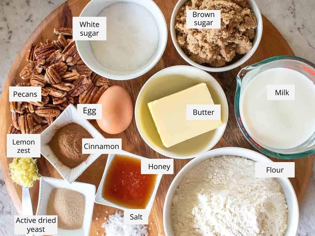ingredients arranged on wooden board - white and brown sugar, milk, flour, salt, honey, butter, yeast, cinnamon, lemon zest, egg and pecans