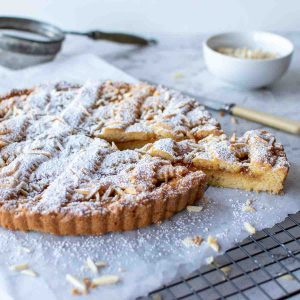 jam tart with lattice top sprinkled with powdered sugar with a slice cut
