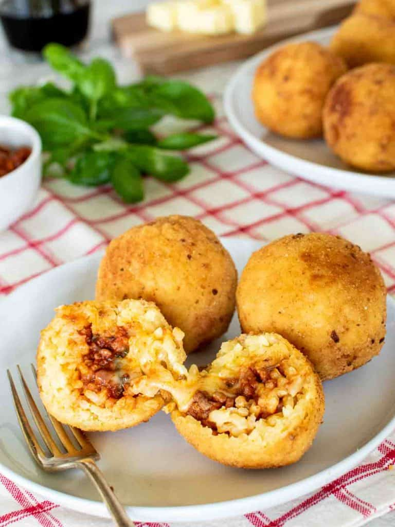 2 whole arancini and one split on a white plate with fork; arancini and basil in the background