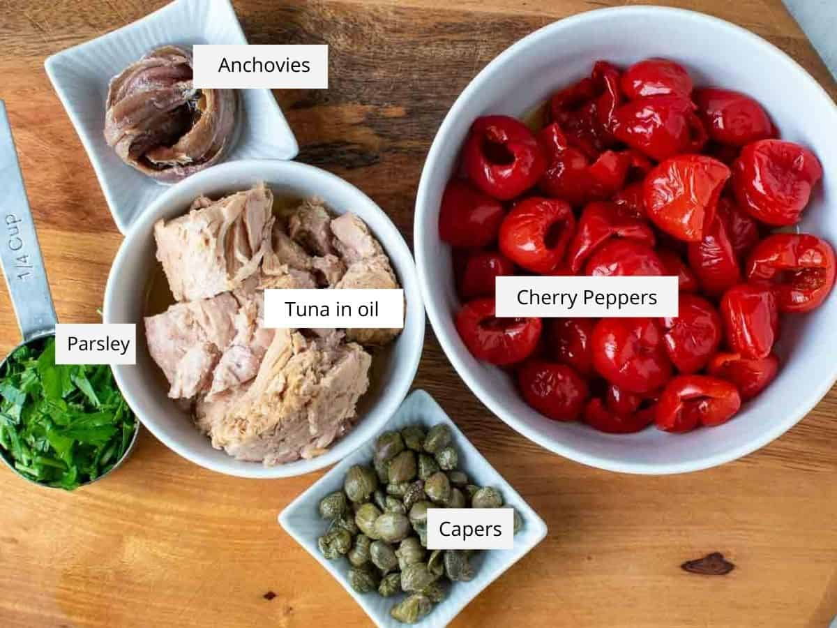 canned tuna in oil, anchovies, pickled red cherry peppers, capers and chopped parsley viewed from above