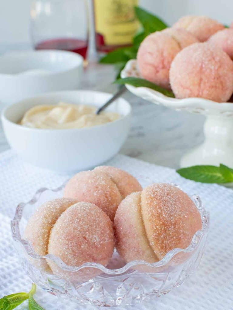three Italian peach cookies in glass bowl with more cookies in the background
