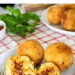 Image with text. Text reads Authentic Italian Arancini. Image is 2 whole arancini and one split on a white plate with fork; arancini and basil in the background