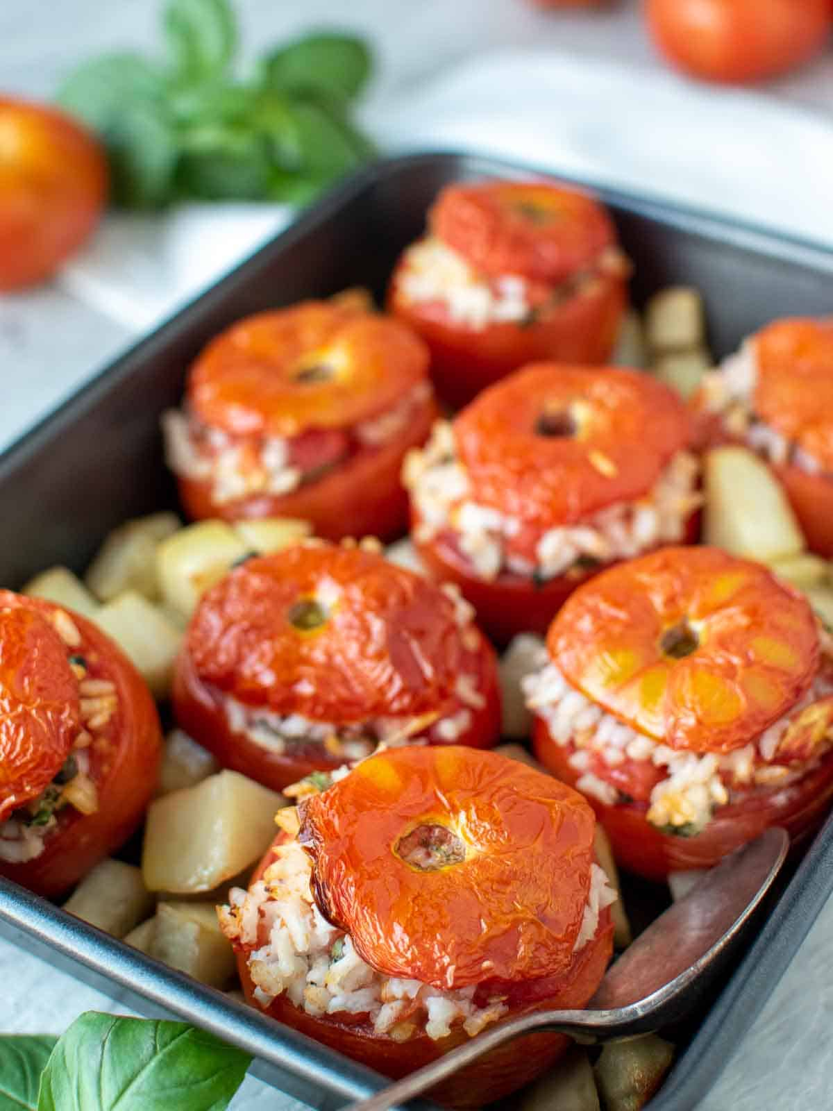 eight baked tomatoes stuffed with rice in black baking pan with cubed roasted potatoes.