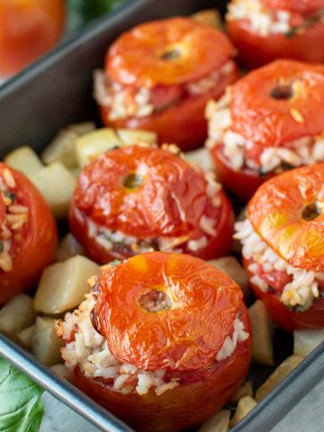 eight baked tomatoes stuffed with rice in black baking pan with cubed potatoes.
