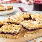 raspberry bars on wooden board with jam and extra bars in the background.
