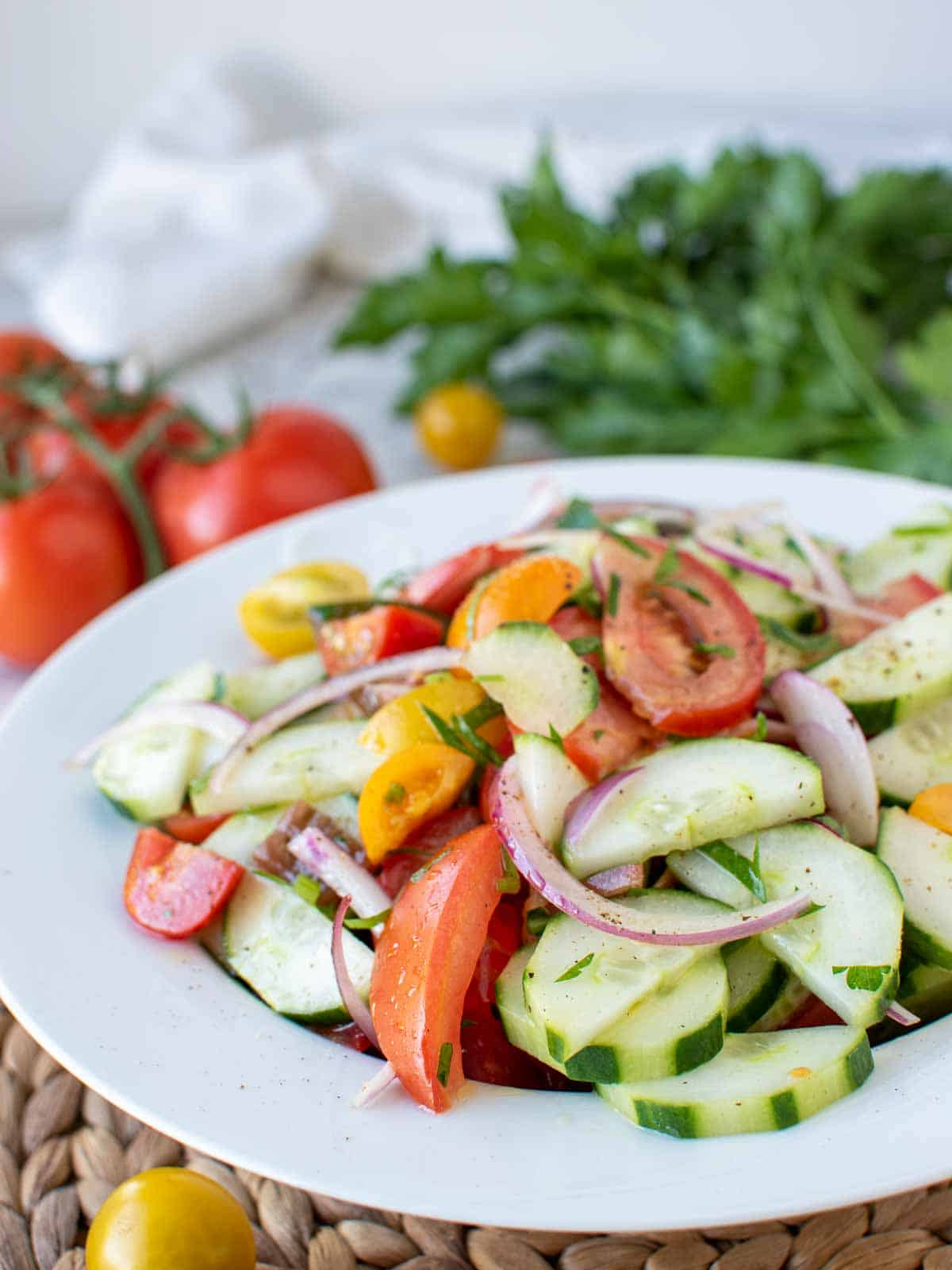 cucumber tomato onion salad on white plate with tomatoes and parsley in the background