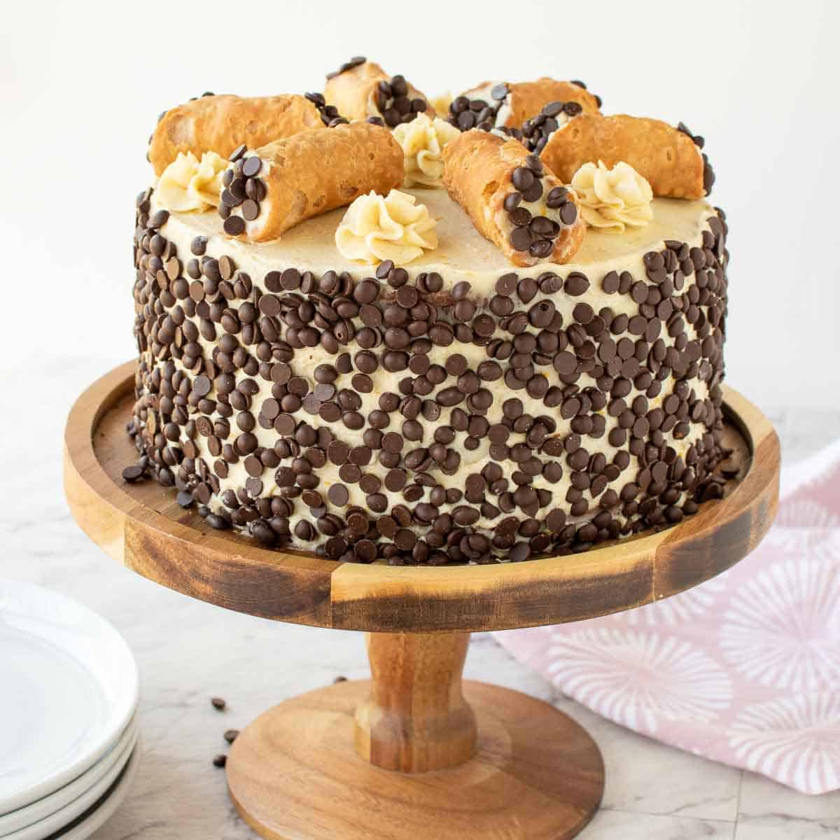 cake covered in mini choc chips with 6 cannoli on top. cake on on a wooden cake stand.