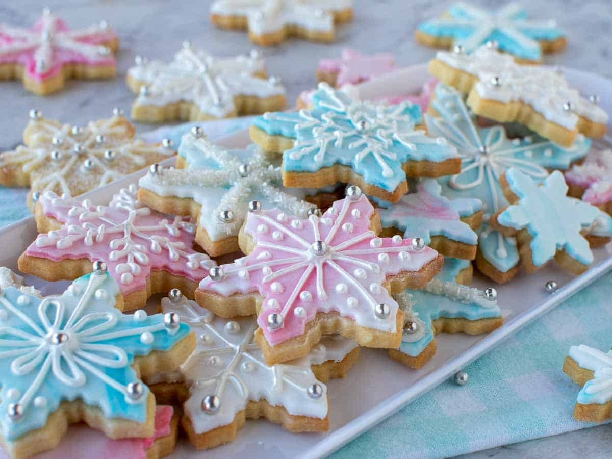 pink, white and blue decorated sugar cookies on white oblong plate.