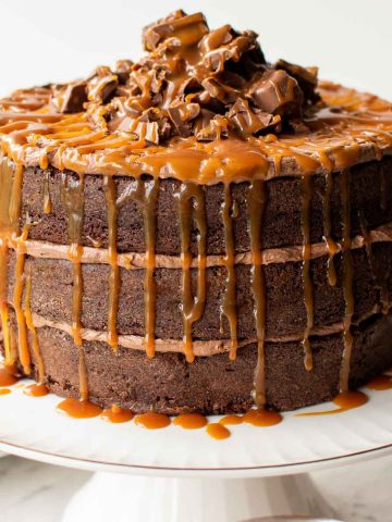 three layer chocolate cake with chocolate frosting and dripping caramel on a white cake stand.