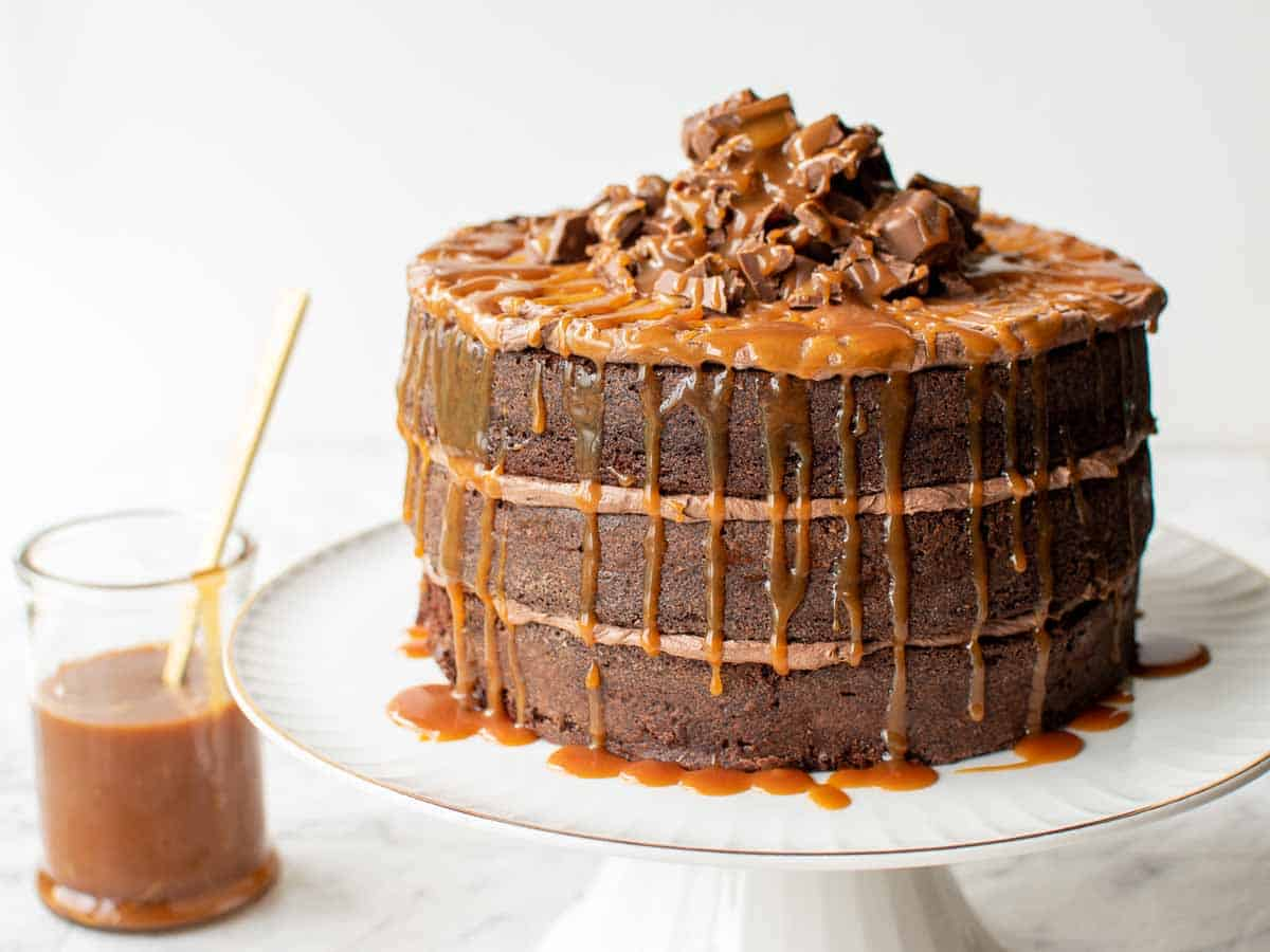 three layer chocolate cake with chocolate frosting and dripping caramel on a white cake stand with jar of caramel in the background.