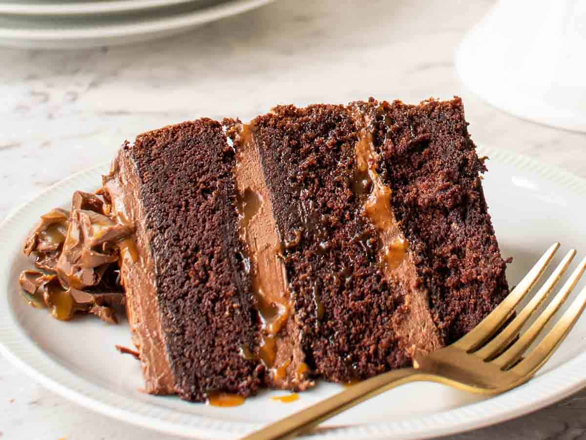 close up of a slice of three layered chocolate cake with chocolate frosting and caramel on a white plate with gold fork.