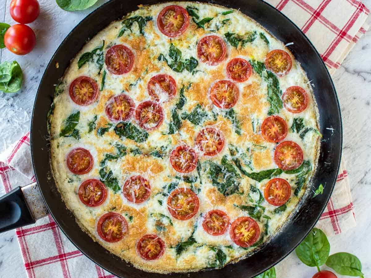 overhead view of egg white frittata with cherry tomatoes and spinach in black frying pan