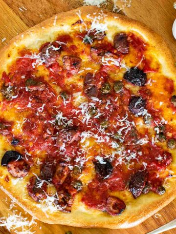 pizza with tomatoes, black olives, anchovies and capers with sprinkling of parmesan viewed from above.
