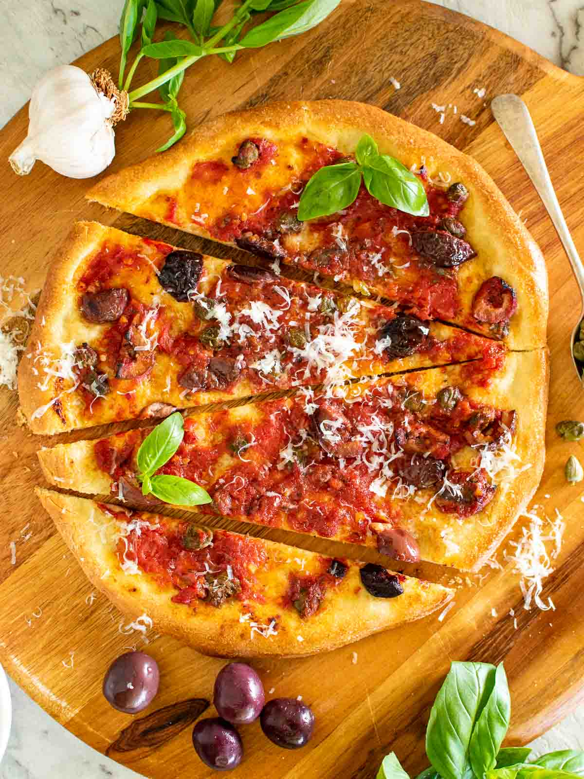 pizza with tomatoes, black olives, anchovies and capers with sprinkling of parmesan cut into four pieces viewed from above.