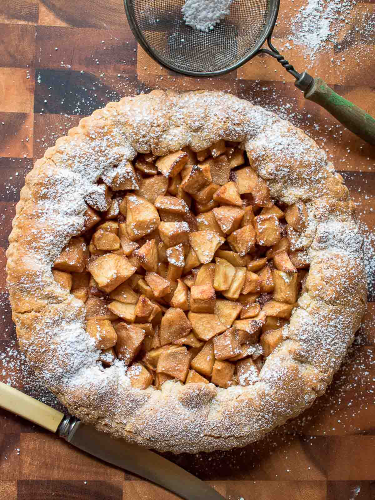 apple crostata dusted with powdered sugar on a wooden board viewed from above.