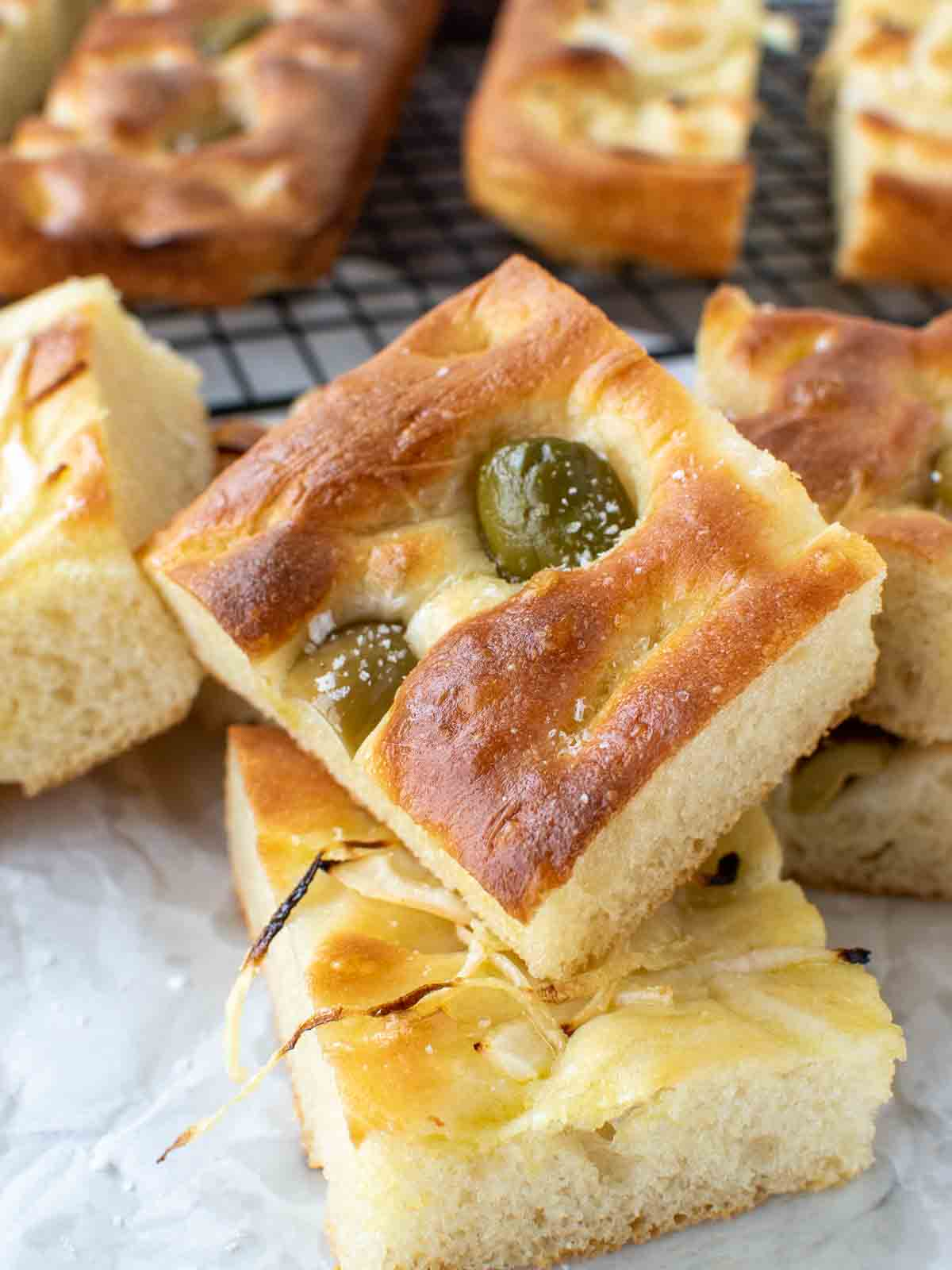 close up of focaccia bread with green olives on top and sliced onions on other pieces with more focaccia in the background