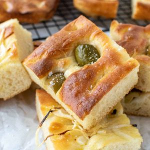 close up of focaccia bread with green olives on top and sliced onions on other pieces